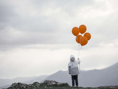 open minded: Small boy with balloons on top of mountain