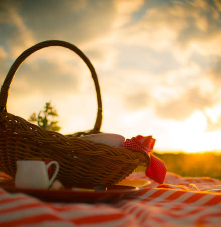 Picnic basket in the meadow at sunset Stock Photo