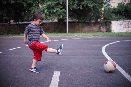 Smal boy kicking the ball in the schoolyard
