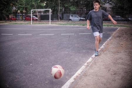 Boy playing football in the schoolyard