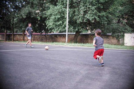 Two brothers playing football in the schoolyard