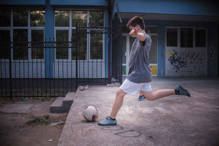 Strong kick of the ball by a young boy in the schoolyard Stock Photo