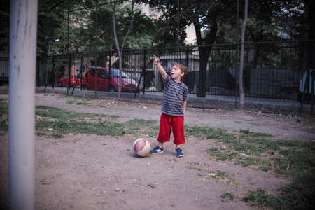 Small boy with football showing at the sky with the finger in the schoolyard