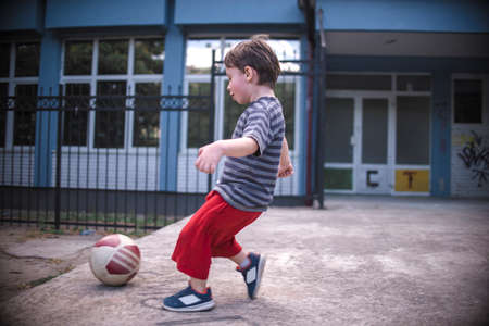 Small boy hitting the ball in the playground Stock Photo