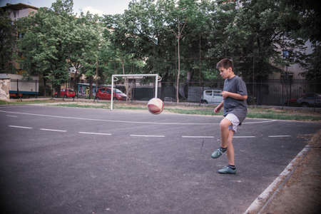 Yound boy kicking the ball in the playground