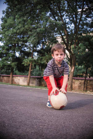 Small boy playing with a ball in the playground