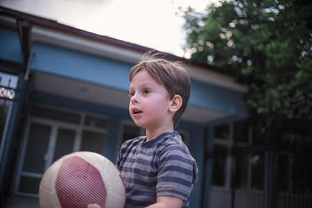 Young boy with a ball in the schoolyard Stock Photo