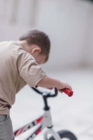 Kid looking down while learning to ride a bicycle Stock Photo
