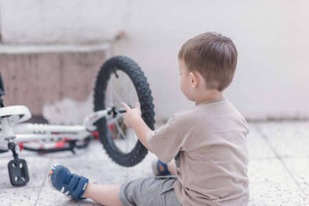 Toddler checking his bicycle tyre