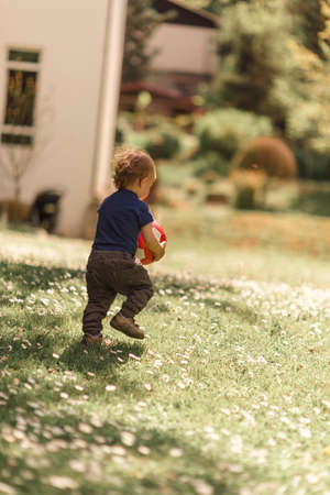 Toddler carrying a ball in the backyard