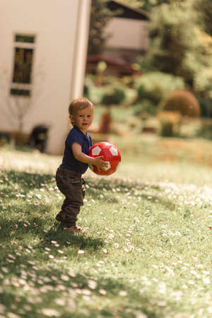 Boy and a ball on a sunny spring day Stock Photo