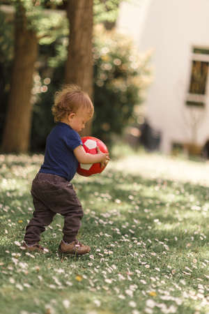 Small boy playing with a ball in the backyard Stock Photo
