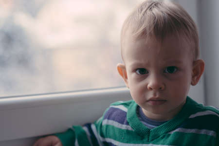 Toddler disturbed while looking at the snow outside of the window Imagens