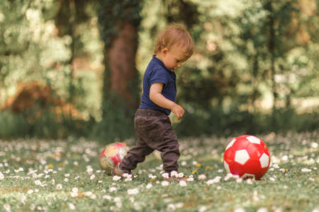 Boy toddler playing with football in the grass
