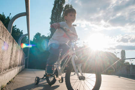 Kid riding a bicycle with sunflares Stock Photo