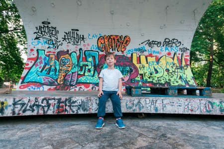 Kid smiling at camera for portrait on the stage with graffiti Stock Photo