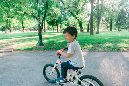 Kid looking back while riding a bicycle in the park