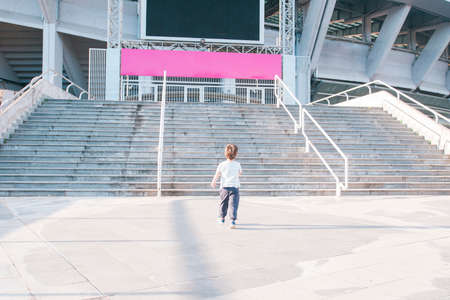 Kid approaching stairs of a big stadium Stock Photo