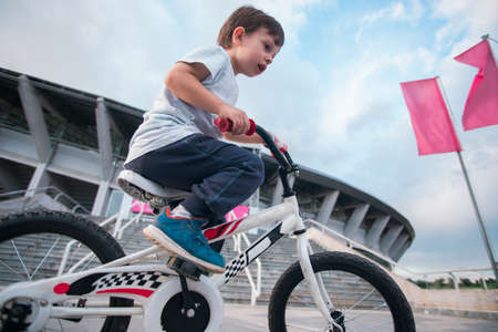 Kid riding a bicycle with low angle photo