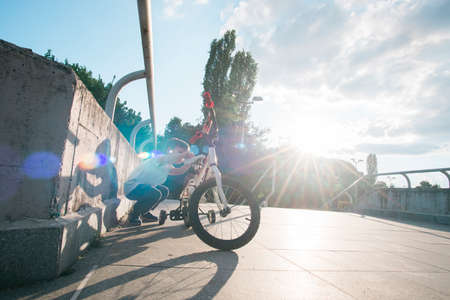 Young boy checking a bicycle shot against the sun