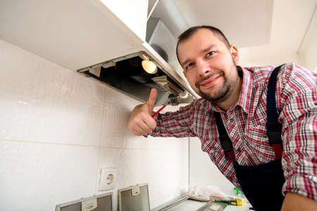 Handyman repairing the kitchen cabinets giving thumbs up