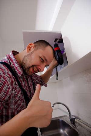 Handyman repairing the kitchen cabinet Stock Photo