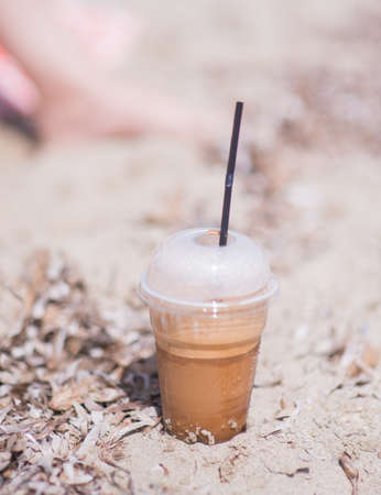 Plastic mug full of coffee with a straw standing on the beach sand
