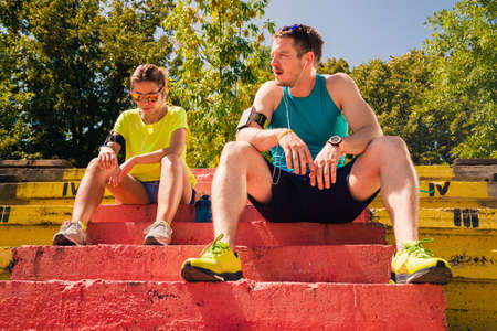 Healthy couple with headphones rest after running Stock Photo