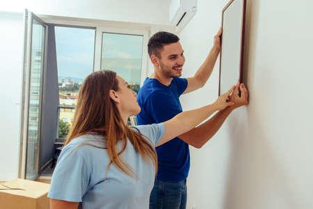 Paar schmückt ihre neue Wohnung mit Malerei an der Wand