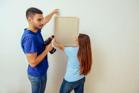 Paar schmückt ihre neue Wohnung mit Malerei an der Wand Standard-Bild