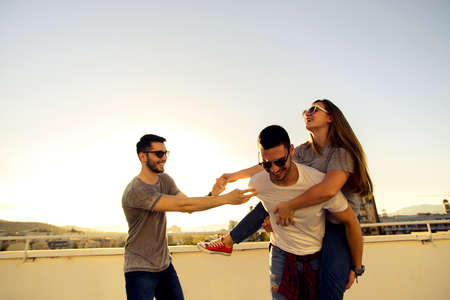 Friends hanging out on the rooftop of the skyscaper and having fun on beautiful sunset Stock Photo