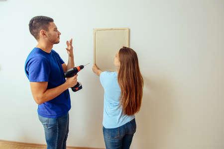 Glückliche junge Familie, die Platz für Bild im Wohnzimmer zu Hause wählt