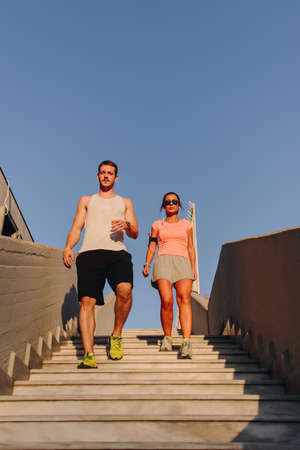 Fitness couple running through the downstairs at urban place