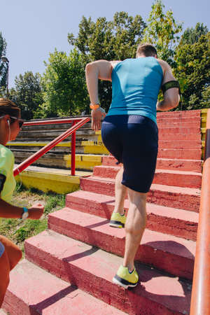Sporty man and woman warming on stairs before jogging Stock Photo