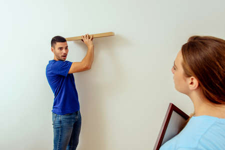 Glückliches Paar, das Bild und Regal an der Wand zu Hause hängt