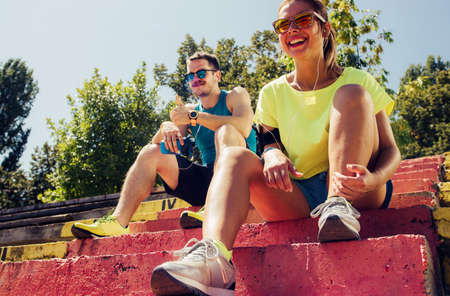 Runners resting taking a break drinking water after running outside