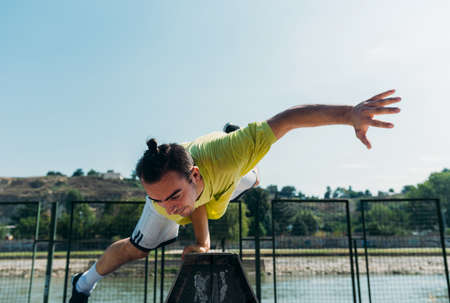 Parkour man maintains a balance with one hand in skatepark Stock Photo
