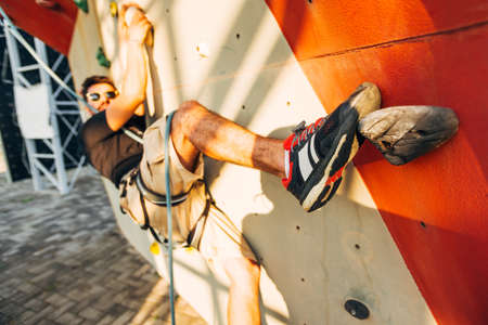 Young climber guy climbing on practical rock in climbing center, bouldering
