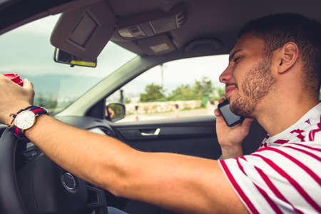 A young man is talking on his cell phone in a car while he is holding a coffee and driving