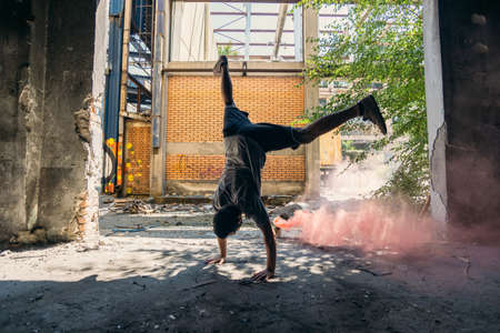 Free runner practicing handstand around red smoke bomb at urban place
