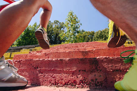 Man and woman muscles legs on stairs while running