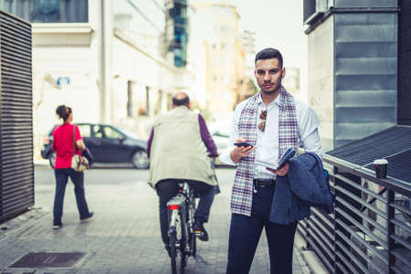 Confident businessman is in public near people who are walking or riding a bike, he is holding opened notebook and looking front