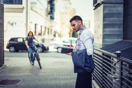 Young successful businessman is standing on the street near a girl who is riding a bike, he is staring at his notebook