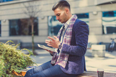 A urban business man is looking amazed at his white tablet while is sitting outside on bench
