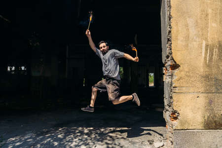 Sporty guy training while jumping with firework candle Archivio Fotografico