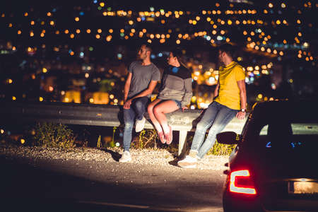 Friends are sitting on the road guardrail at night enjoying the city panorama and lights