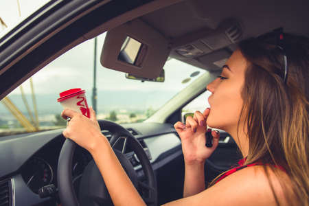 Young female is sitting in her car while is doing her makeup on the car mirror Imagens
