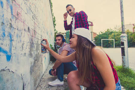 Three friends hanging out near old wall, trying to paint graffiti Фото со стока