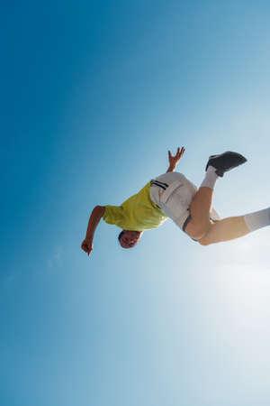 Parkour man below blue sky doing parkour tricks