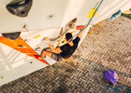 Young sporty man is bouldering in a climbing hall 写真素材